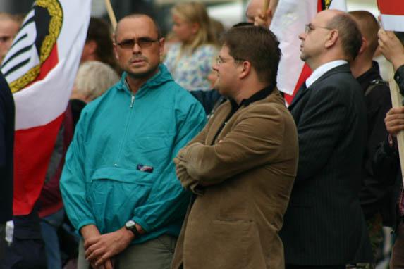 Rocco Kilz (in türkis) als Personenschützer des NPD-Fraktionsvorsitzenden in Sachsen Holger Apfel (Mitte) zusammen mit NPD-Vize Peter Marx (rechts) am 15.08.2005 auf einer Kundgebung in Dresden.