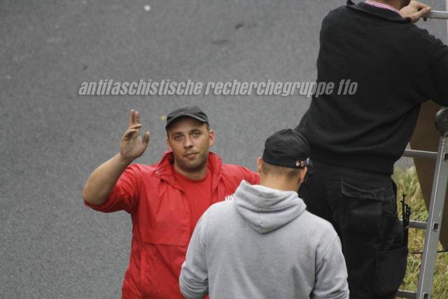 NPDler Frank Odoy (in Rot) begrüßt die ihn beobachtenden Antifaschist_innen.