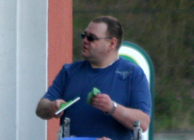 """Einer, der sich zu verbergen versucht: Maik Wilke beim Fenster putzen seines Geschäfts """"Nordic Company"""" am Bahnhofsplatz 3."""
